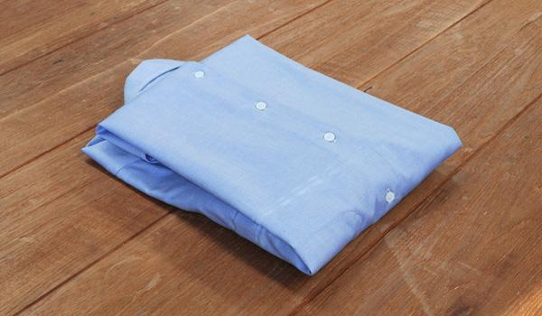 ワイシャツのたたみ方10:長く飛び出している裾の部分を肩のラインで折りこみます。