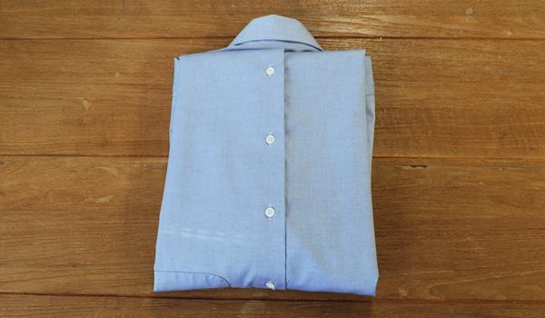 ワイシャツのたたみ方11:裾に向けて細く折っていますので、折り返しても裾部分が肩のラインからはみ出さずに綺麗にシャツ幅に収まっています。