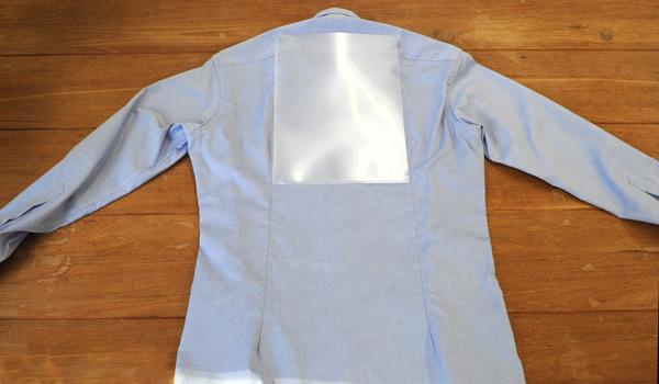 ワイシャツのたたみ方16(クリアファイルを使う方法):裏返したらシャツの中心にA4サイズのクリアファイルを入れます。