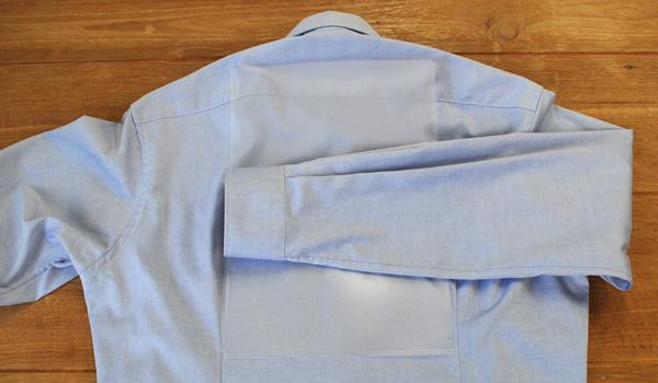 ワイシャツのたたみ方17(クリアファイルを使う方法):片方の袖をクリアファイルの端までまで折り返します。