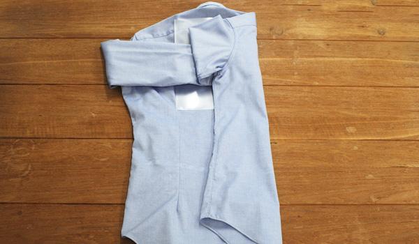 ワイシャツのたたみ方19(クリアファイルを使う方法):クリアファイルを包み込むように、クリアファイルの幅で半分の身頃を折り畳みます。クリアファイルがあると裾に向けて細く折り返すのは難しいですができる範囲で細くなるようにたたんでみましょう。