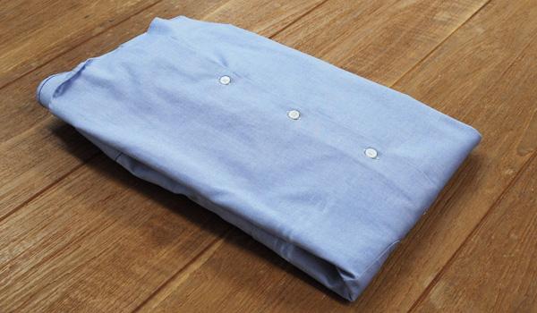 ワイシャツのたたみ方21(クリアファイルを使う方法):クリアファイルの下のところまで裾を折り返します。