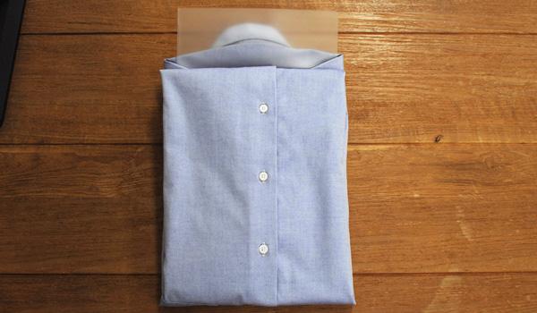 ワイシャツのたたみ方22(クリアファイルを使う方法):長く飛び出している裾の部分を肩のラインで折りこみます。セットしていたクリアファイルを抜きます。