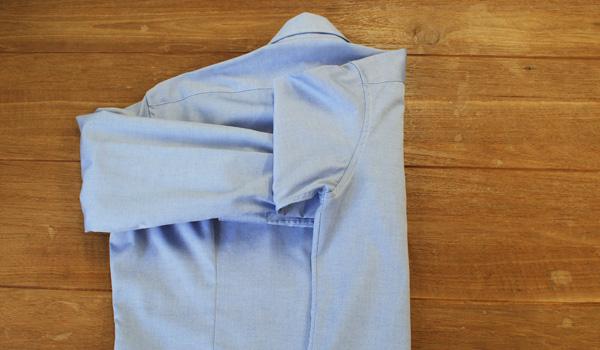 ワイシャツのたたみ方5:青い線の背ダーツのラインで半分の身頃を折り畳みます。背ダーツラインがないシャツは、首から肩の縫い合わせまでの(肩幅)半分くらいまで折りかえす。