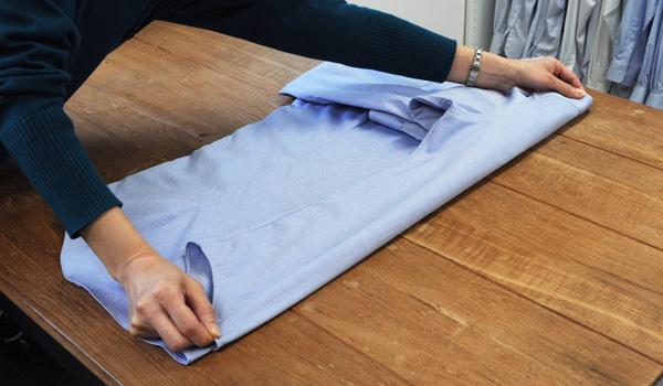 ワイシャツのたたみ方6:この時のポイント(^^)!裾に向けて少し細くなるように多めに折り返すと後程綺麗な仕上がりになります。また、折り返したら肩部分と裾を持ち軽く引っ張りシワを伸ばします。