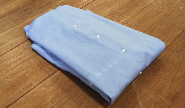 ワイシャツのたたみ方8:ポケットの下あたりでシャツを折ります先ほど裾に向けて細く折りかえしましたので、裾が肩幅よりも少し内側に入っています。